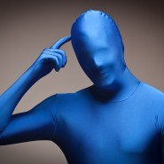 Man Wearing Full Blue Nylon Bodysuit Scratching His Head on a Grey Background.