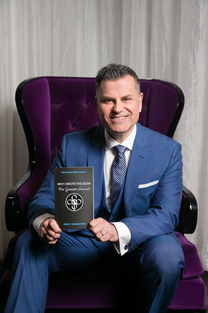 JK seated holding copy of book
